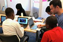 Teacher Mike Mannix meets with students writing on their laptops
